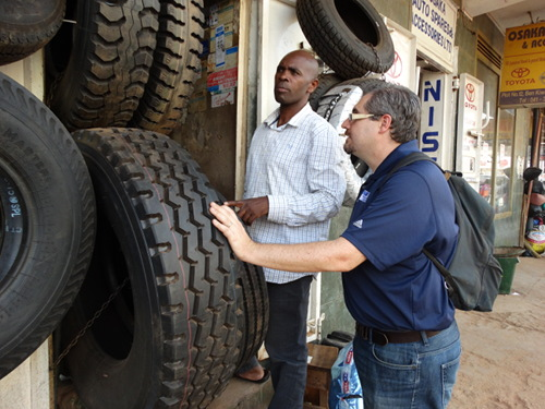 Rob Freedman and Apollo Kaagwa purchasing the tires for the school van in Kampala Uganda